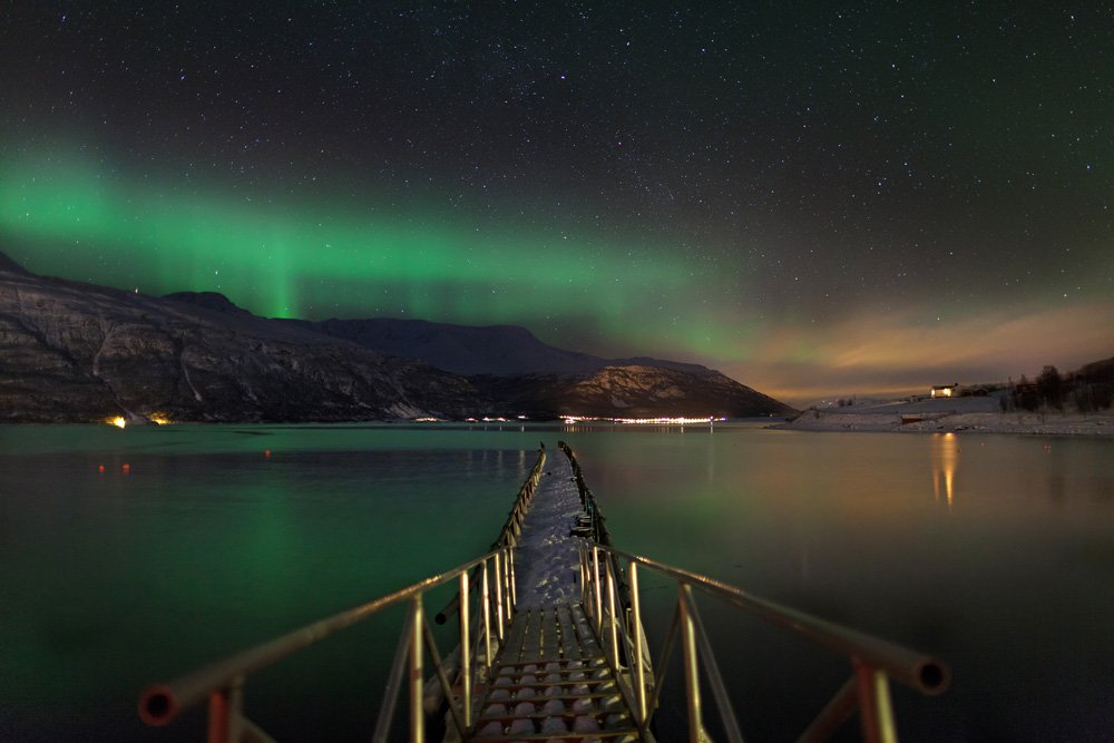 Northern lights in the sky, a pier over a fjord in the surroundings of Tromso, Norway